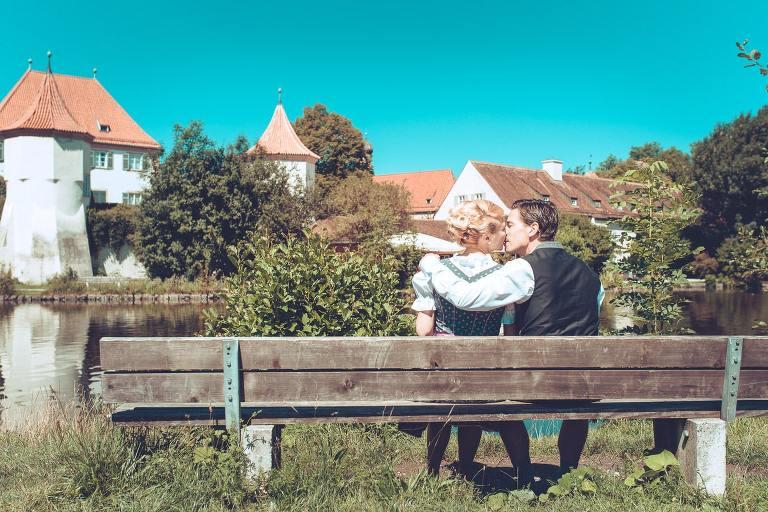 Hochzeitspaar auf Parkbank bei Schloß Blutenburg